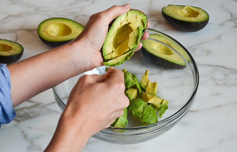 scooping avocado flesh into bowl