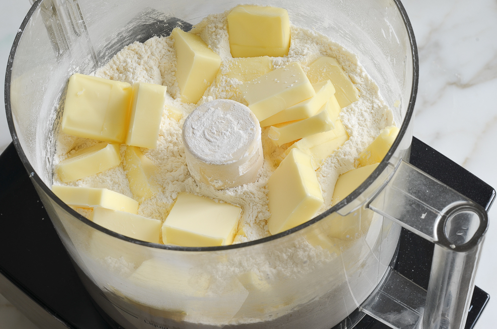 adding pieces of butter to food processor