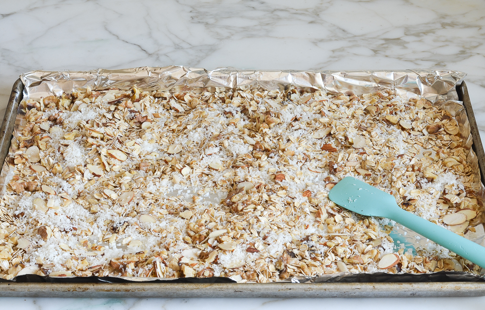 adding shredded coconut to baking sheet