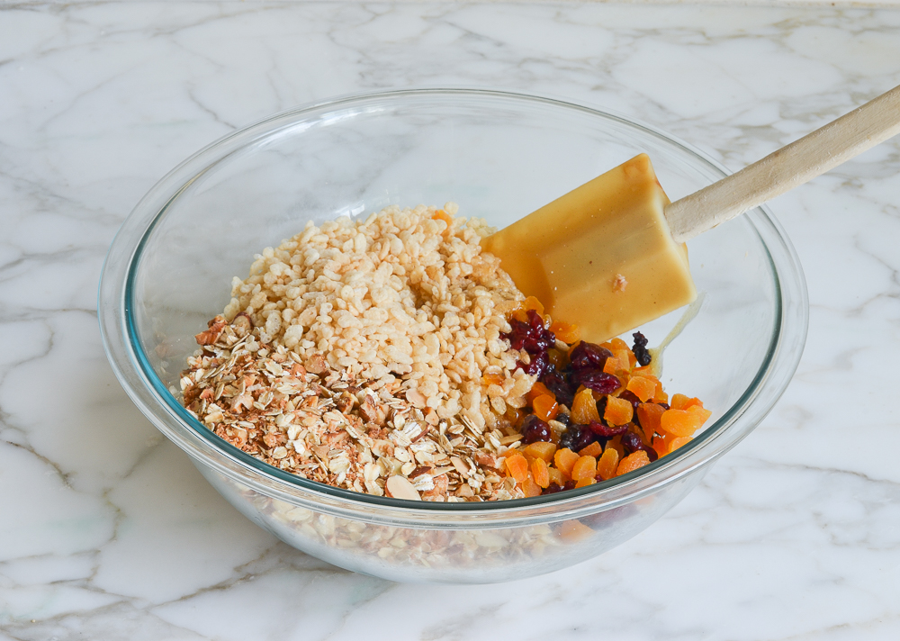 oats mixture, rice cereal, dried fruit, and honey mixture in large bowl