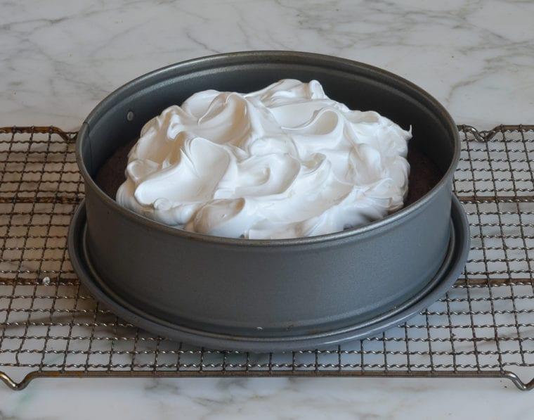 swirling meringue over baked cake