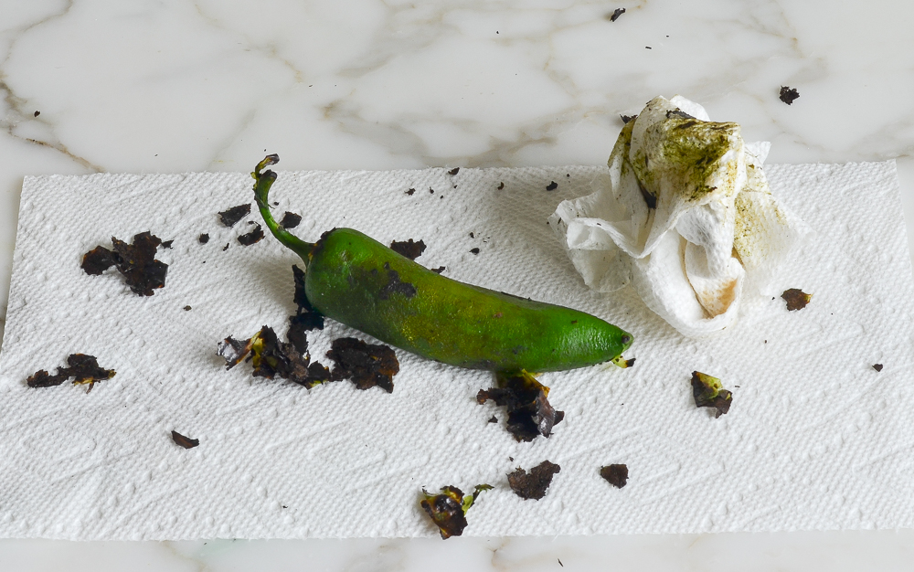 scraping the charred skin off of the jalapeno