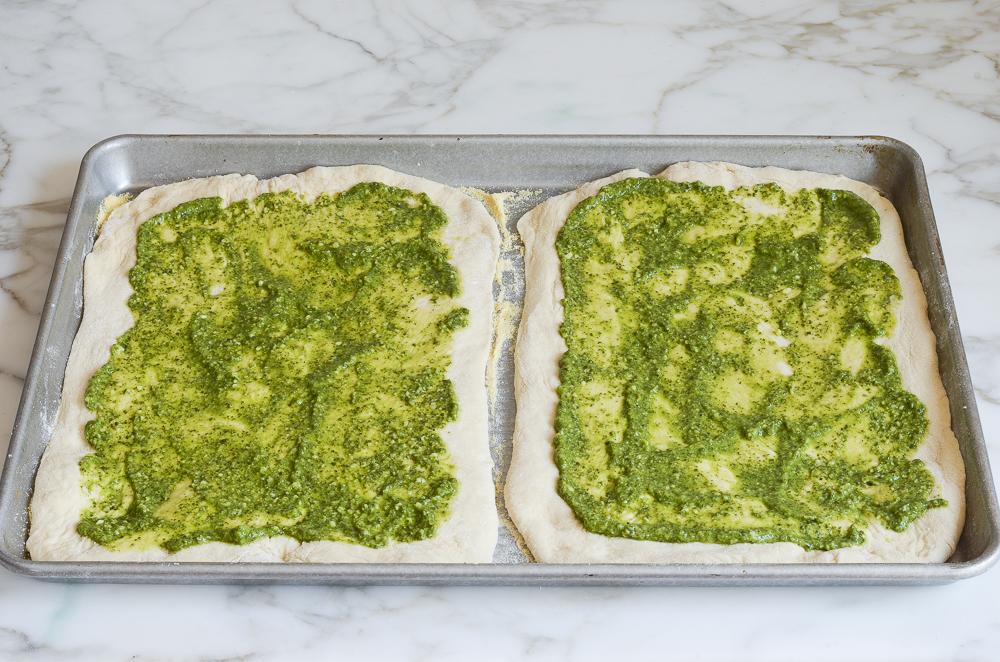spreading pesto on pizza dough