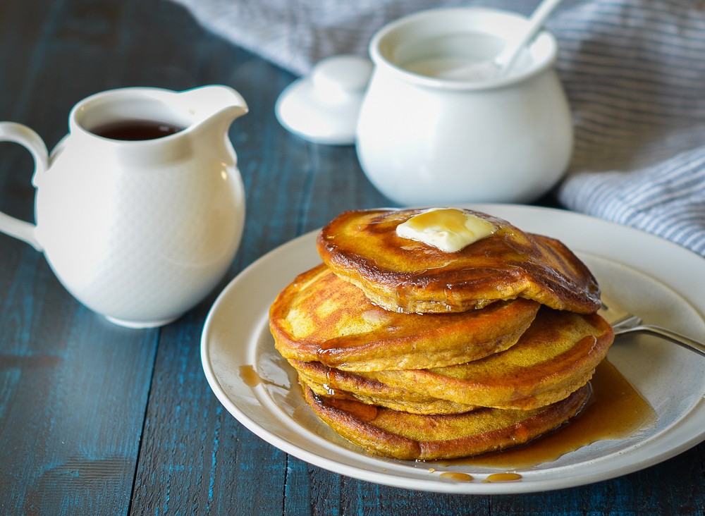 pumpkin pancakes on a plate with maple syrup and butter