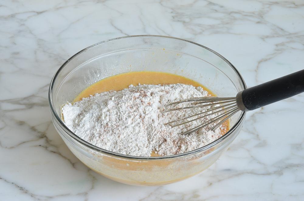 adding dry ingredients to wet ingredients for pumpkin pancakes