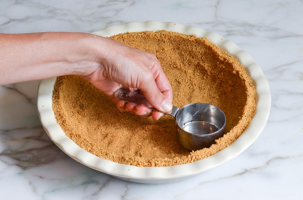 pressing the graham cracker crust into pie pan