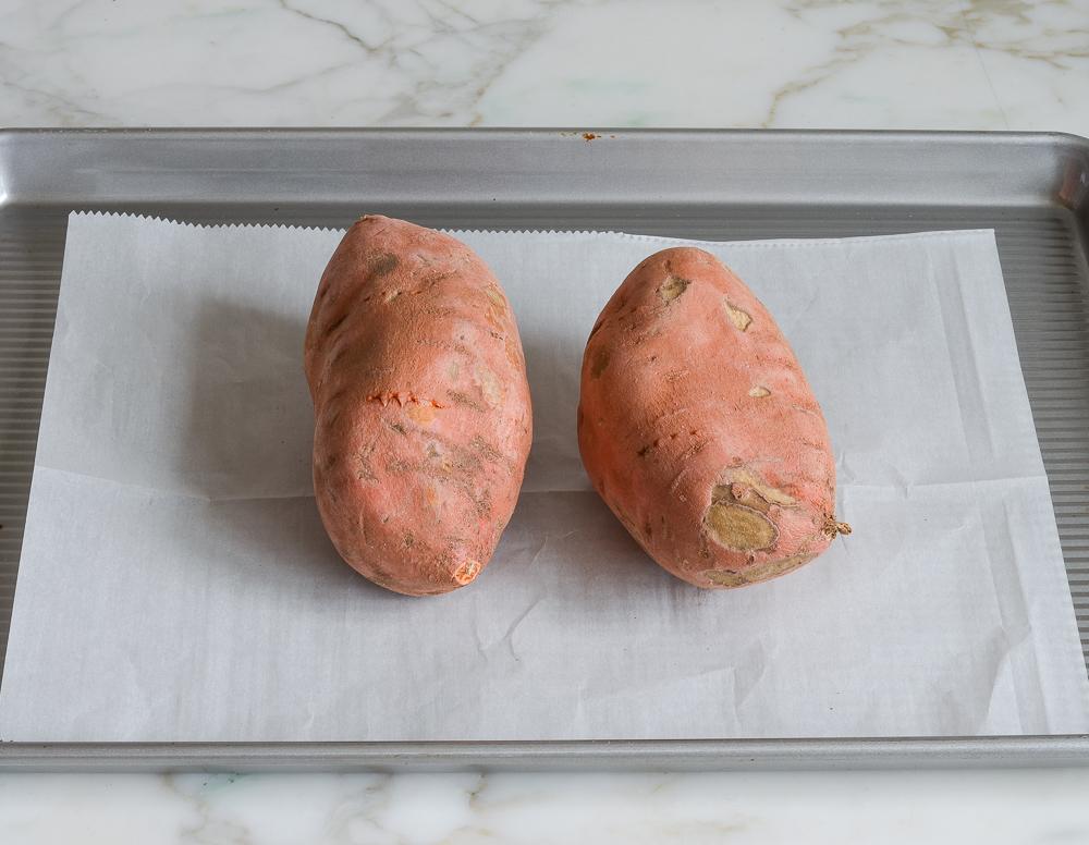 poked sweet potatoes on baking sheet