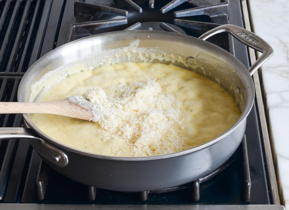 adding cheese to cream sauce