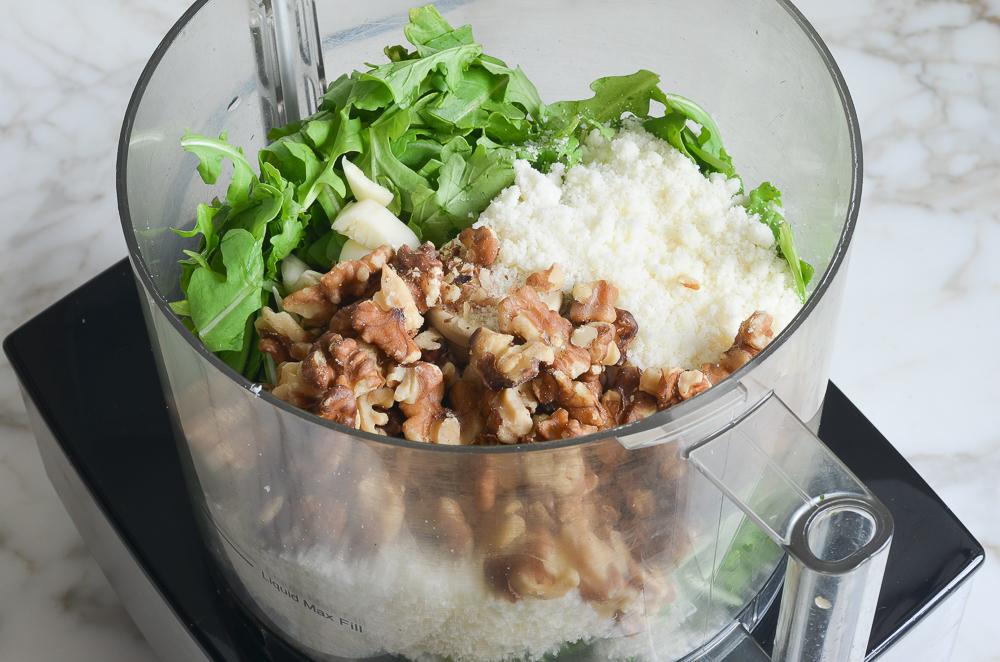 arugula, walnuts, cheese, and garlic in food processor