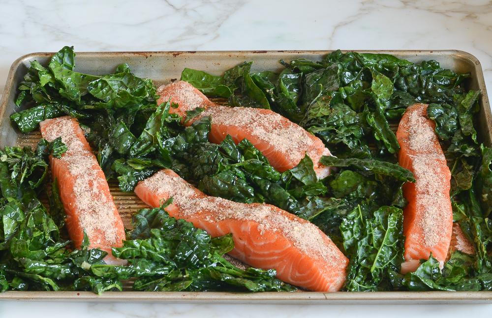 kale and salmon arranged on sheet pan ready to bake