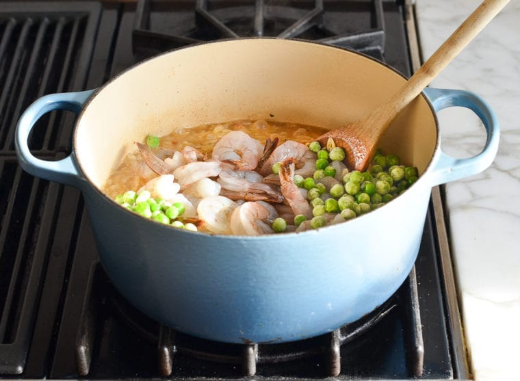 adding shrimp and peas to the pot