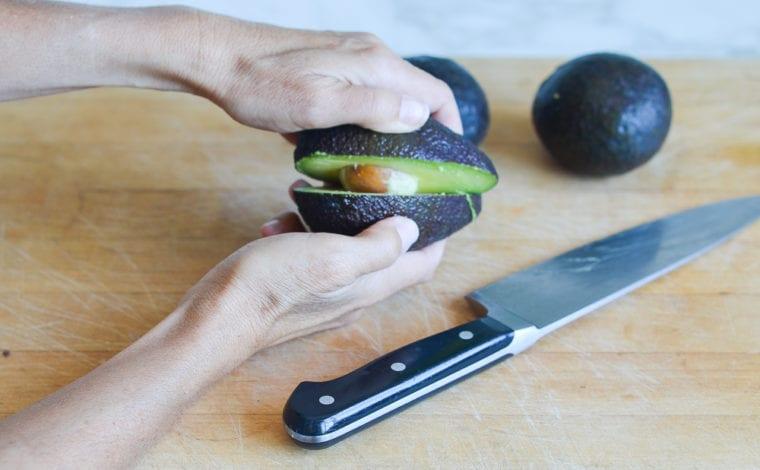 pulling the avocado halves apart