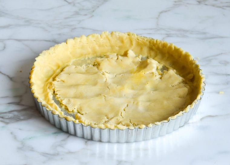 pressing pate sucree into tart pan