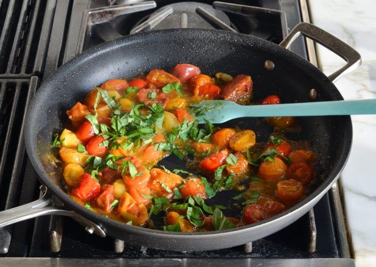 finishing cherry tomato sauce with basil