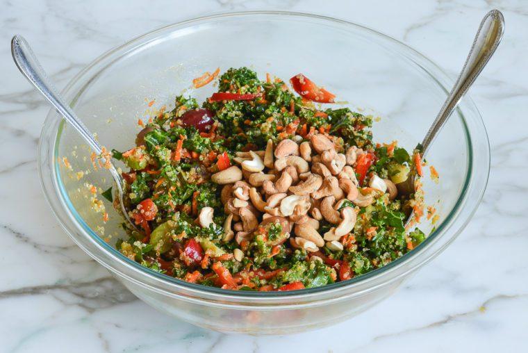 adding cashews to quinoa salad before serving