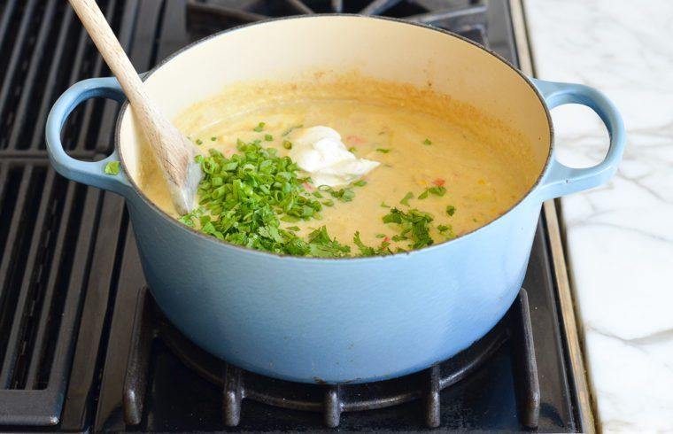 adding scallions, cilantro, and sour cream to corn chowder