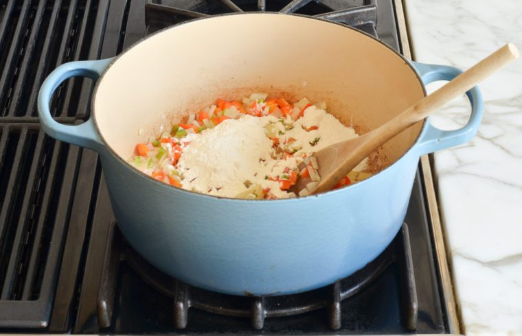 adding flour to vegetables